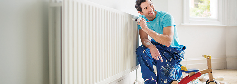 Man in overalls painting radiator