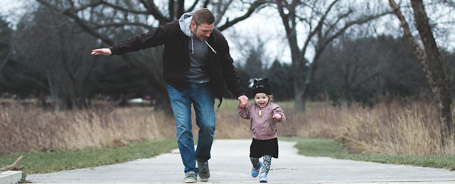 Father walking with daughter in park
