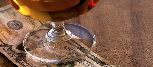 An American 5 dollar bill underneath a glass of beer