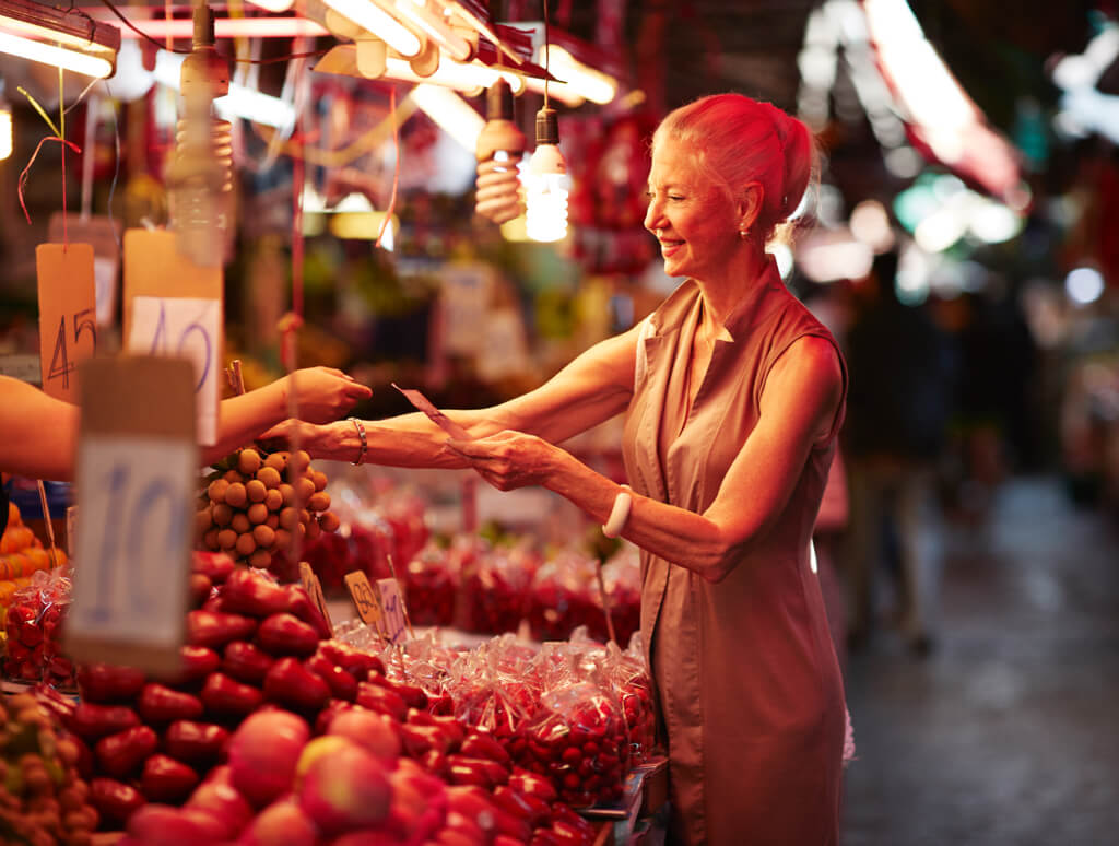 woman buying vegetables from a night market