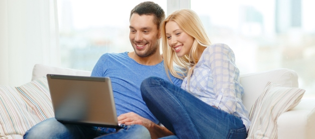 Man and woman on sofa using a laptop