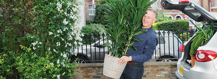 Man carrying plants into home