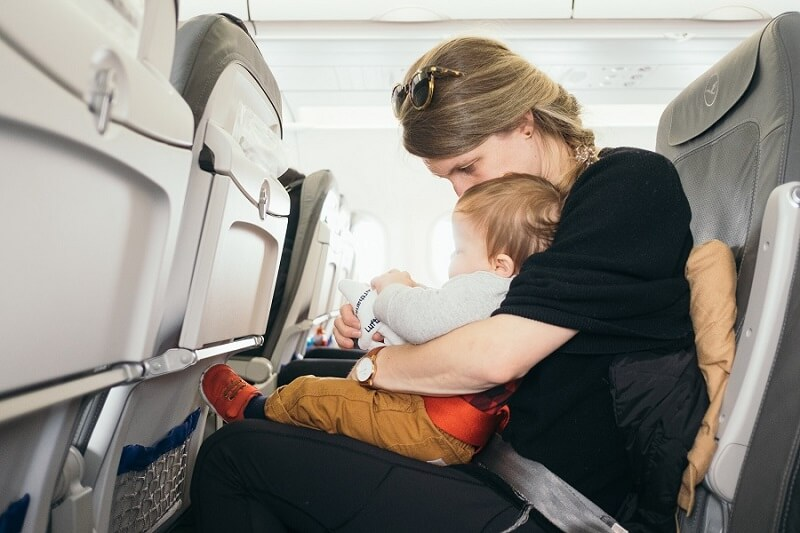 A mother sits on a plane with her baby on her lap