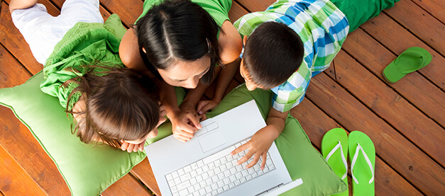 Young family playing with a laptop outside on decking
