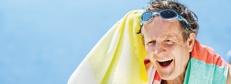 Man on beach with towel and googles