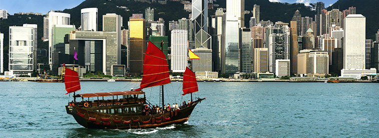 Boat sailing in river with view of skyline in Hong Kong