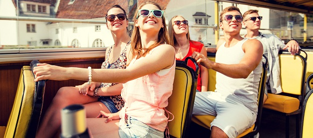 A group of friends on the top deck of a tourist bus